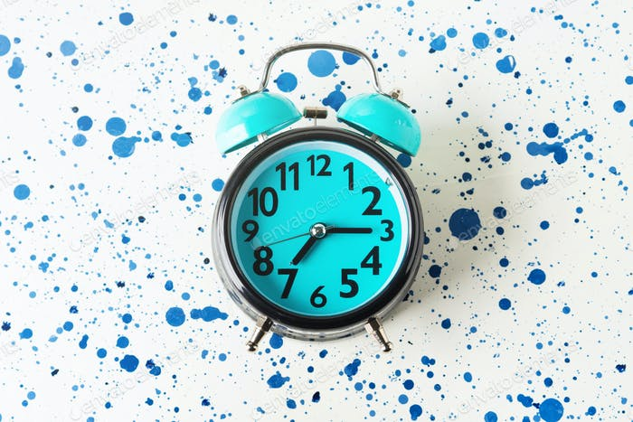 Blue alarm clock on abstract background. Flat lay