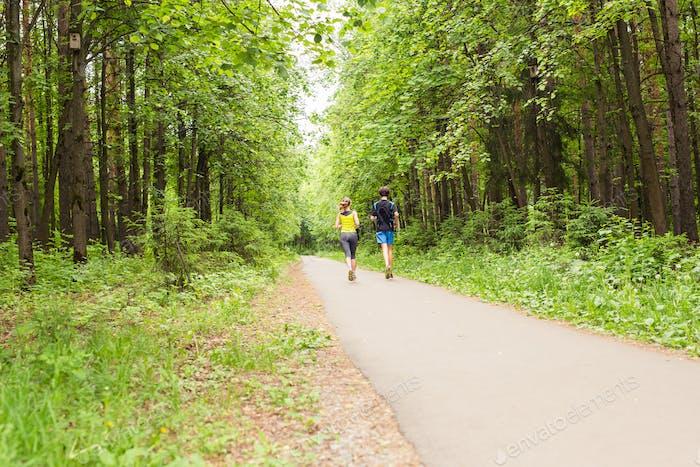Fitness, Sport, Freundschaft und Lifestyle-Konzept - lächelnde Paar läuft im Freien.