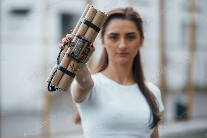 Digitale Elemente. Zeigt eine Zeitbombe. Junge Frau hält gefährliche Sprengwaffe in der Hand