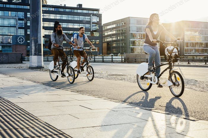 Three people cycling in city
