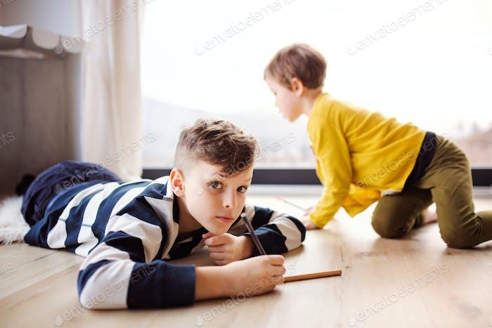 Zwei glückliche Kinder spielen zu Hause, zeichnen.