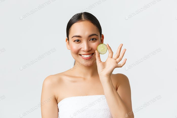 Beauty, personal care, spa salon and skincare concept. Beautiful asian female in bath towel holding