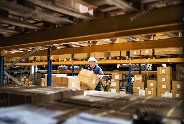 Senior male warehouse worker or a supervisor unloading a pallet truck with boxes.