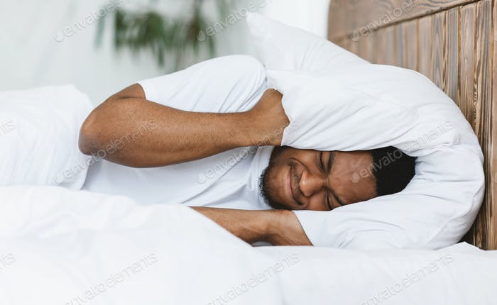 Disturbed Man Covering Ears With Pillow Suffering From Insomnia Indoor