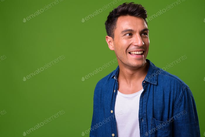 Young handsome Hispanic man against green background