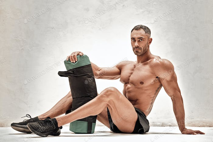 Embossed and exhausted fitness couch posing in a studio with sportsgear