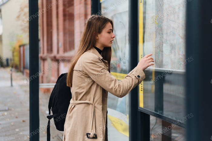 Attractive girl with backpack thoughtfully looking city map on bus stop