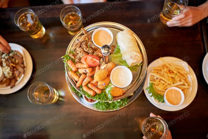 table with food and beer glasses at bar or pub