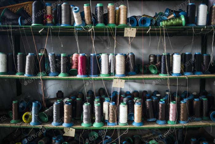 Close up of shelves of colorful thread for sewing shoe soles in a factory.