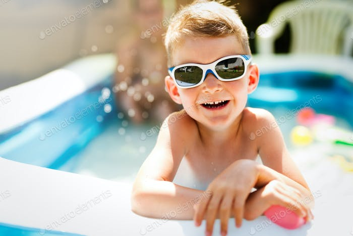 Happy boy enjoying summer time in swimming pool