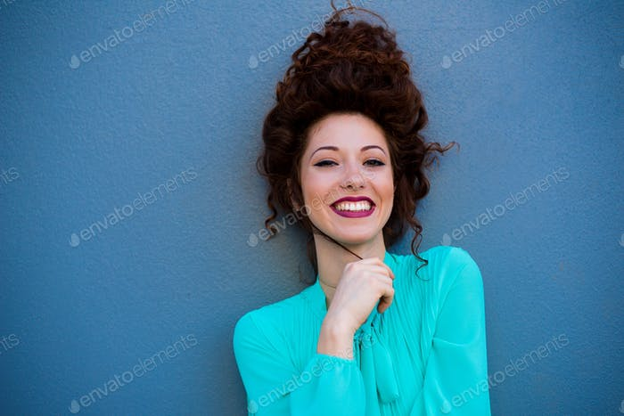 Portrait of a happy beautiful young redhead woman by a colorful