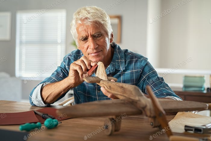 Old man perfecting a handmade wooden plane