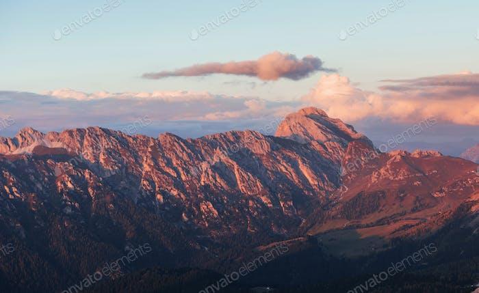 Большие доломитовые горы с деревьями ниже при ежедневном солнечном свете