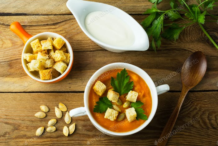 Pumpkin soup with croutons in the white bowl