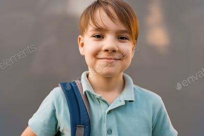 School boy posing a backpack
