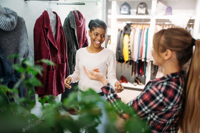 Zwei weibliche Freunde Wahl Mantel im Geschäft, Einkaufen