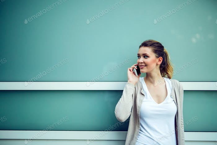 Successful businesswoman or entrepreneur talking on cellphone while walking outdoor