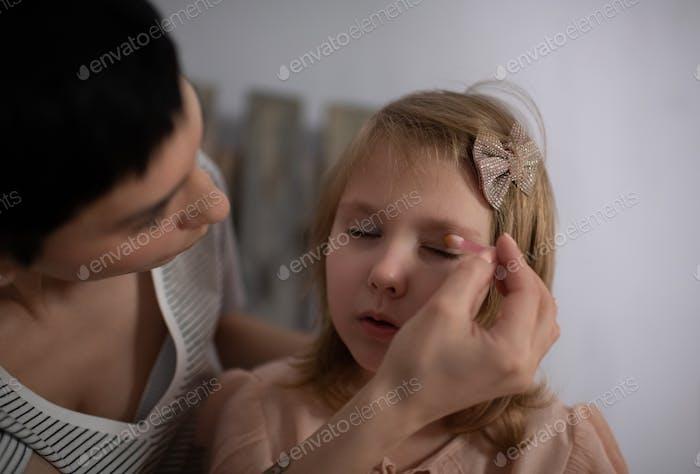 Mutter hilft Tochter, Make-up anzuwenden