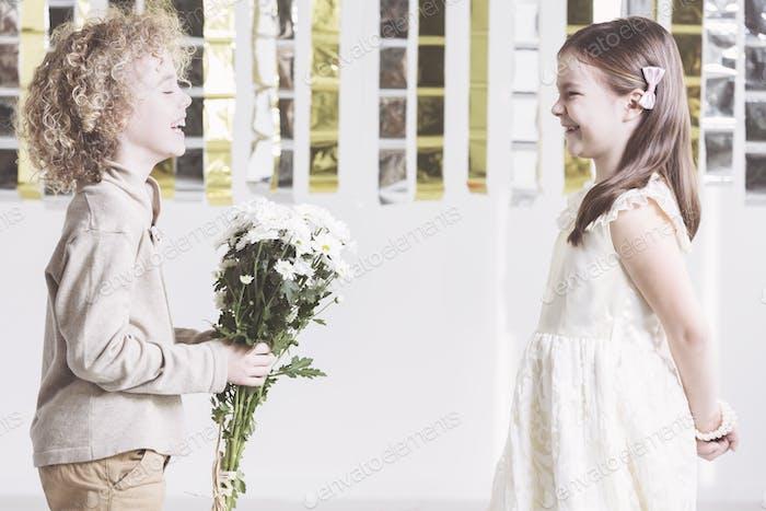Junge geben Blumen zu Mädchen