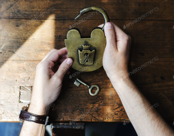 Hands Holding Unlock Padlock and Key on Wooden Table