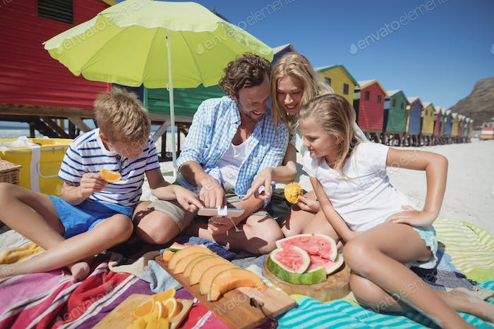 Happy family sitting together by fruits on blanket at beach