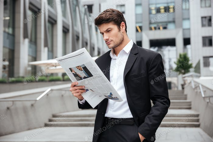 Businessman standing and reading newspaper outdoors