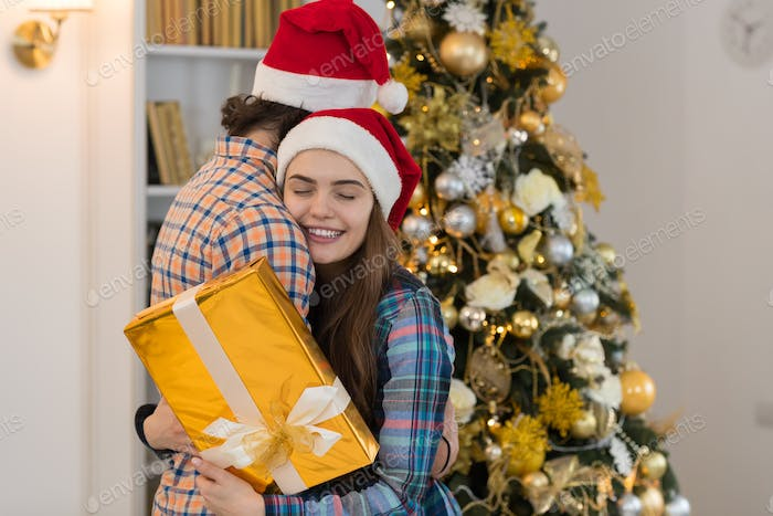Christmas Holiday Happy Couple Wear New Year Santa Hat Cap, Man And Woman Embracing Near Decorated