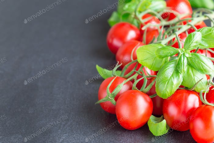 Cherry tomatoes with basil leaves on dark slate background, hori