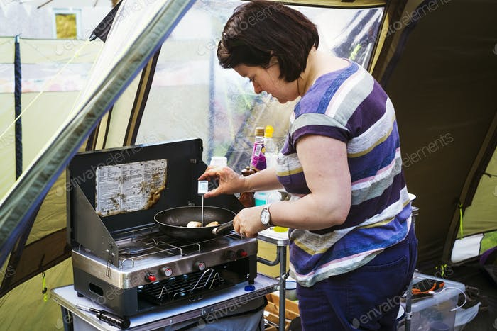 Woman standing at a camping stove, measuring the temperature of a scallop in a frying pan with a