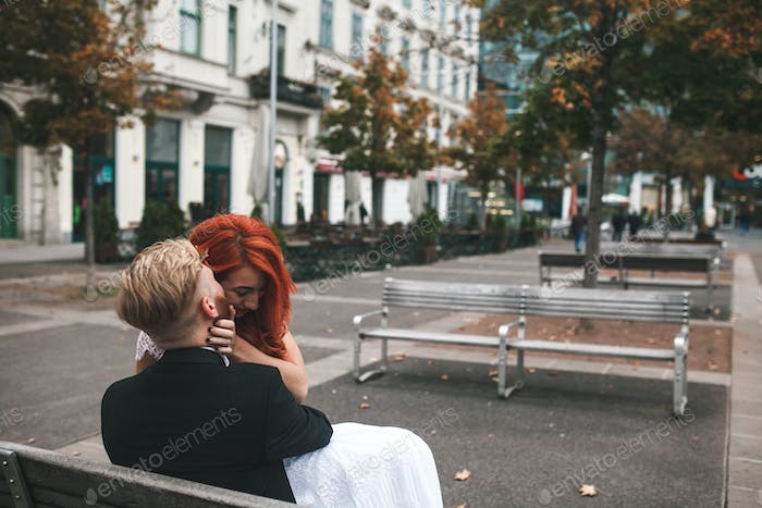 Wedding couple sitting on a bench in a futuristic building