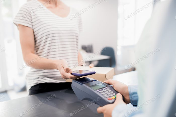 Woman Paying by Smartphone in Shop