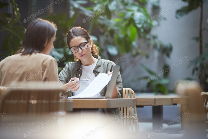 Two Women Discussing Business Project in Cafe