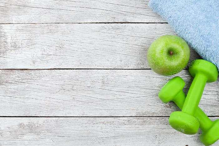 Fitness concept. Dumbbells, apple and towel