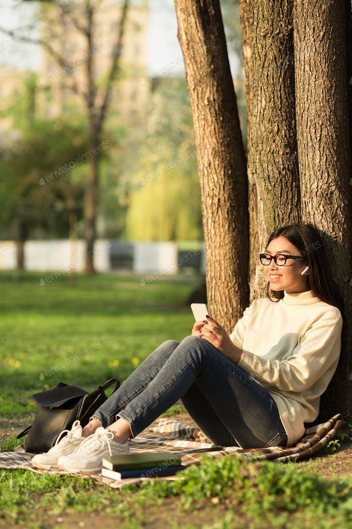 Female student using phone, sitting under tree in parkland