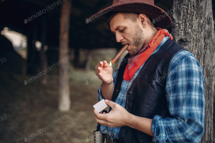 Brutal cowboy lights a cigar with matches