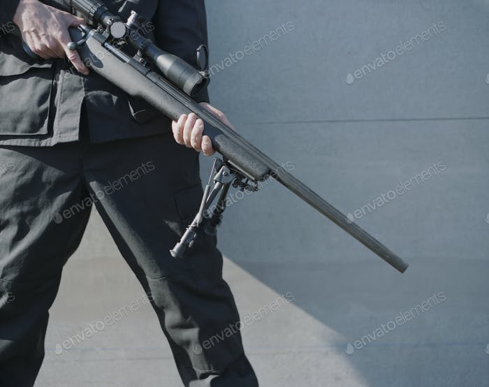 Man in armed forces holding high powered sniper riifle