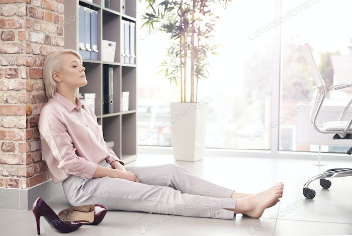 Businesswoman with eyes closed resting on floor