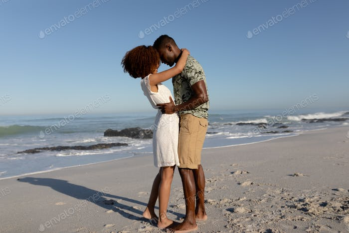 Happy couple embracing each other on the beach