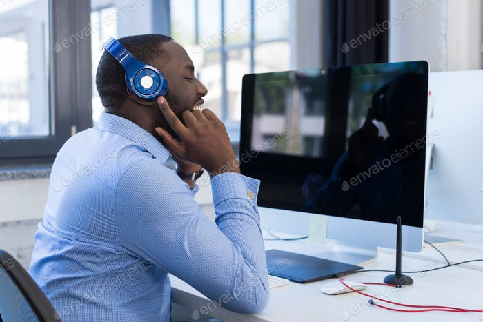 African American Businessman Listen To Music With Headphones In Modern Coworking Space, Adult