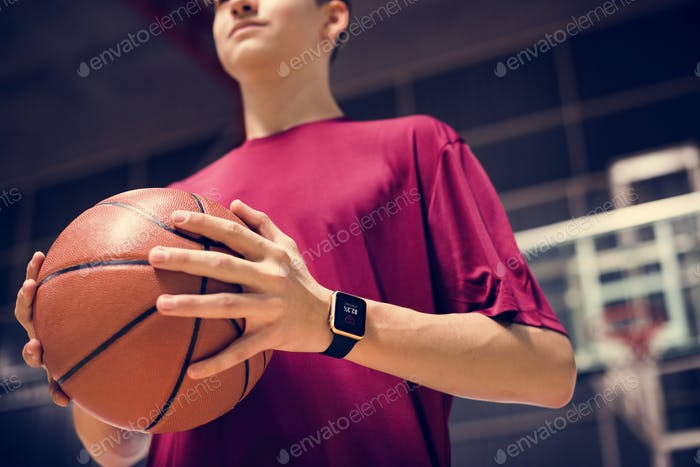 Teenage boy holding a basketball on the court