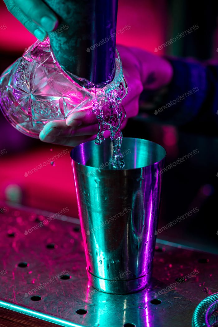 Close up of barman finishes preparation of alcoholic cocktail, pouring drink in multicolored neon