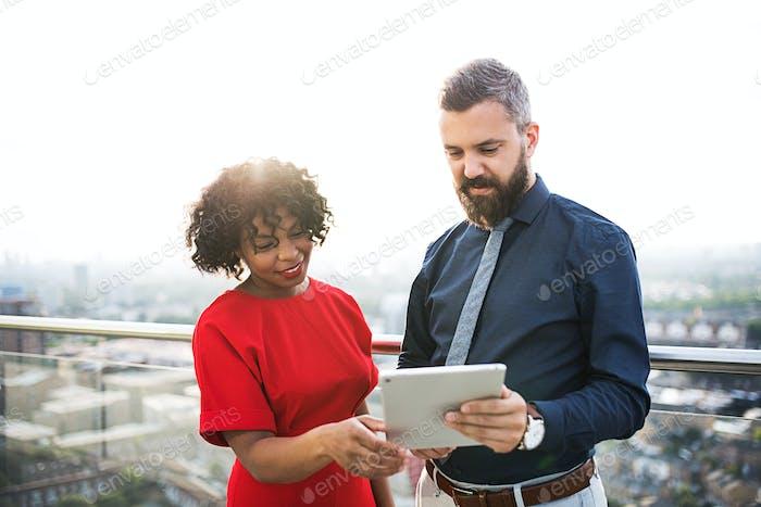Un Vertical de dos empresarios con tableta de pie frente al panorama de Londres.