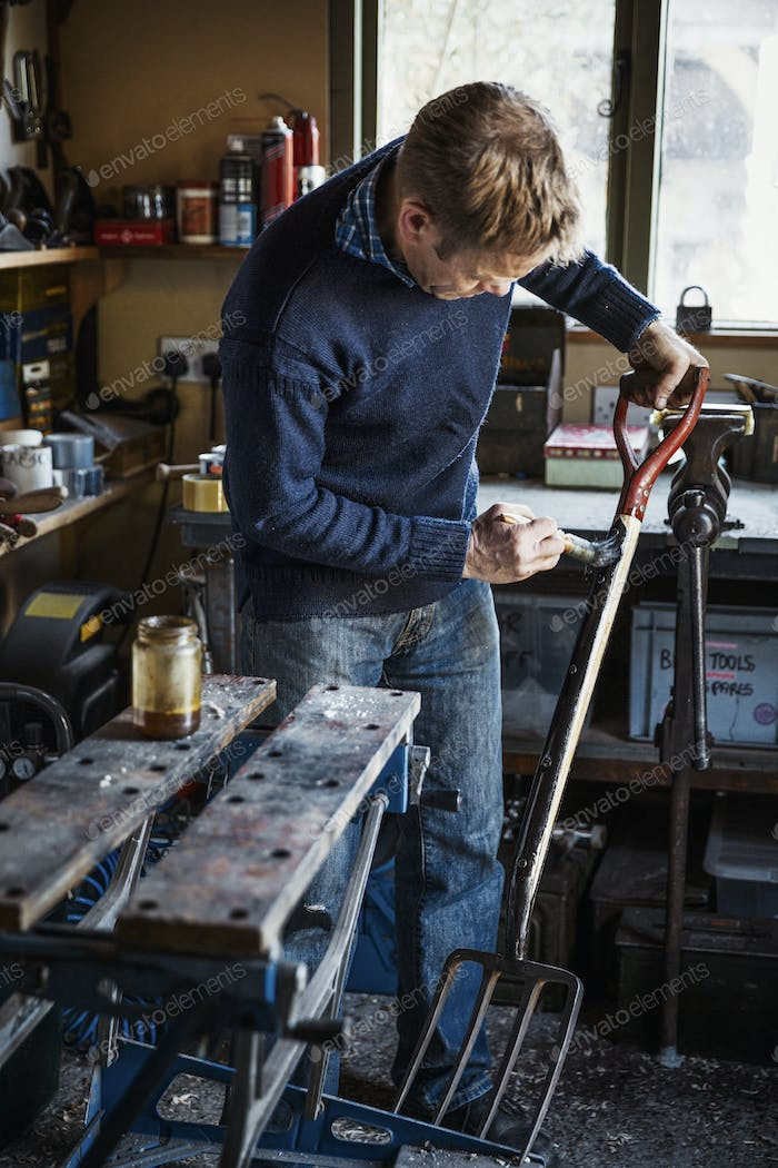 Man standing in a workshop oiling the handle of a metal garden fork with four tines.