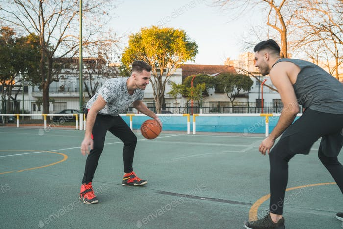 Two young friends playing basketball.