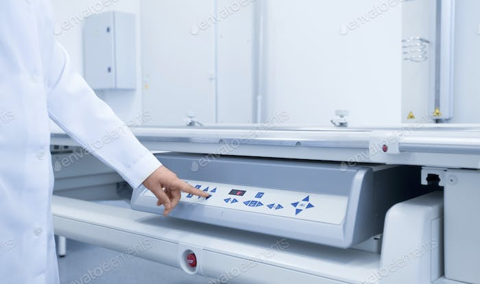 Doctor in medical gown starting X-ray machine