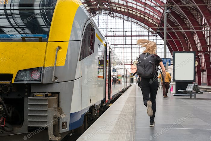 Female tourist with backpack running to the train