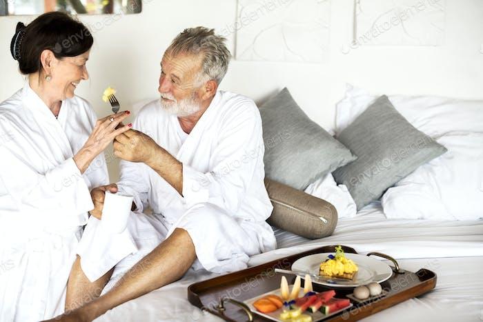 A senior couple enjoying room service