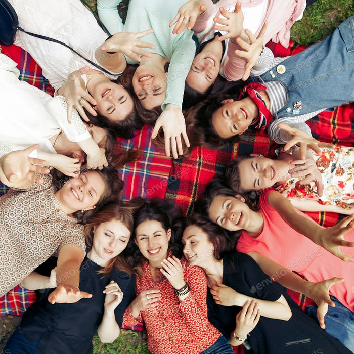 happy group of women faces in circle posing and smiling on picnic