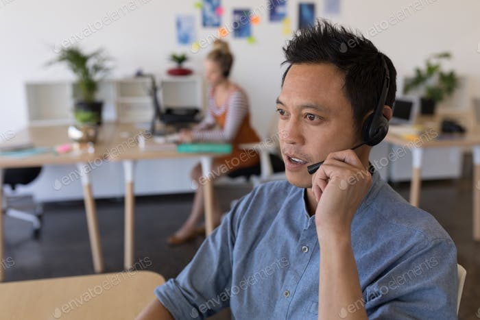 Side view of Asian male executive looking into distance while talking on headset at desk in office