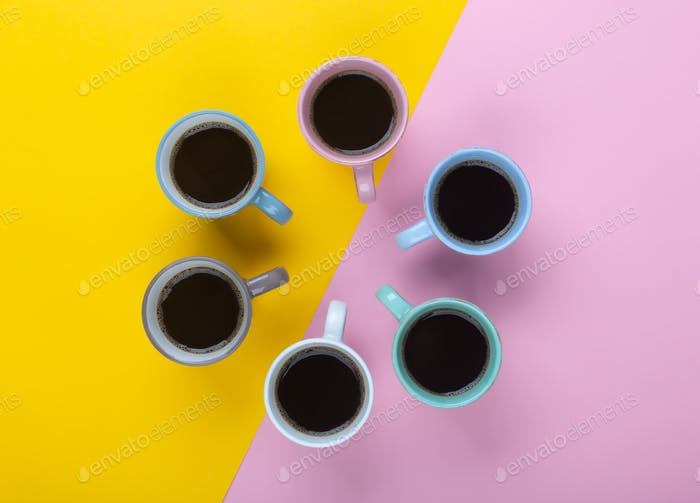 Coffee in the different cups on the pink and yellow background. Flatlay, cheerful day concept